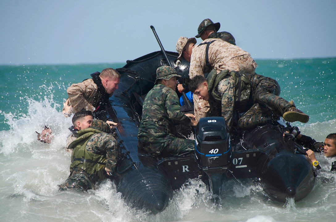 Troops jump onto an inflatable boat maneuvering in white ocean water.