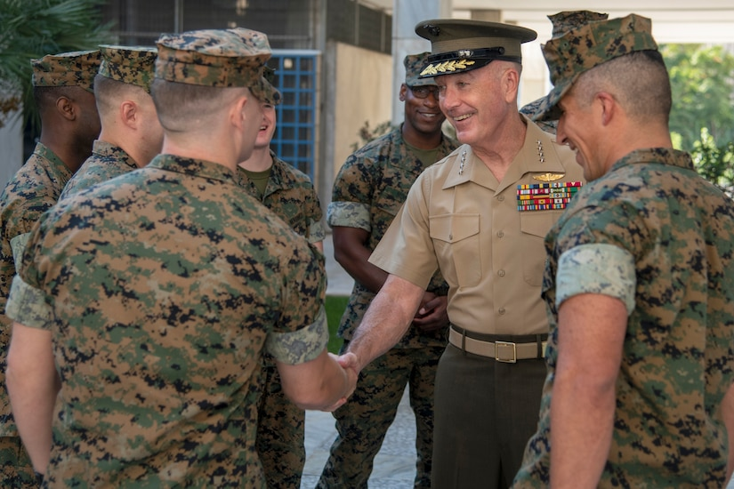Marine Corps Gen. Joe Dunford shakes hands with a Marine as others gather around them.