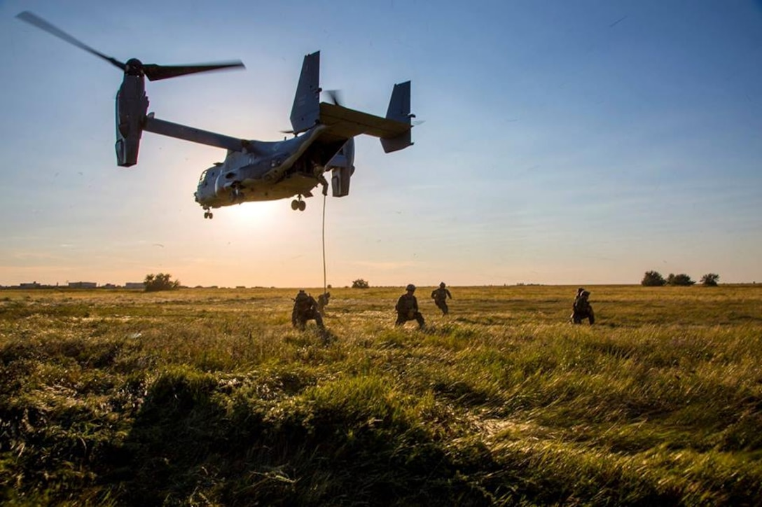Service members kneel in a field as an Osprey hovers overhead.