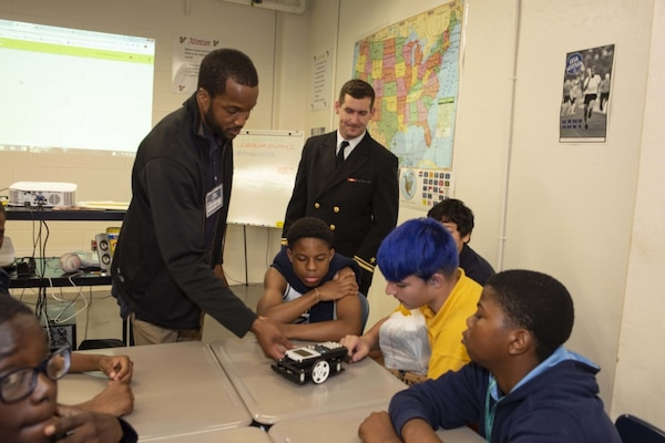 Sailors assigned to the Ohio-class ballistic missile submarine USS Maryland (SSBN 738) and engineers from Naval Surface Warfare Center, Carderock Division demonstrate calculator-controlled robots to Navy Junior Reserve Officers Training Corps students at Mergenthaler Vocational Technical Senior High School as part of Maryland Fleet Week and Air Show Baltimore. Calculator-controlled robots are part of Carderock's Division's science, technology, engineering and math outreach program and teaches students to program the robots to carry out a variety of tasks. MDFWASB is Baltimore's celebration of the sea services and provides an opportunity for the citizens of Maryland and the city of Baltimore to meet Sailors, Marines and Coast Guardsmen, as well as see firsthand the latest capabilities of today's maritime services. (U.S. Navy photo by Martin Sheehan/Released)