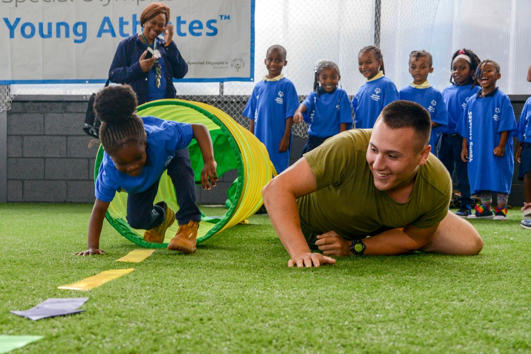 A Marine crawls on grass next to a little girl emerging from an obstacle as a line of children and one adult watch smiling.