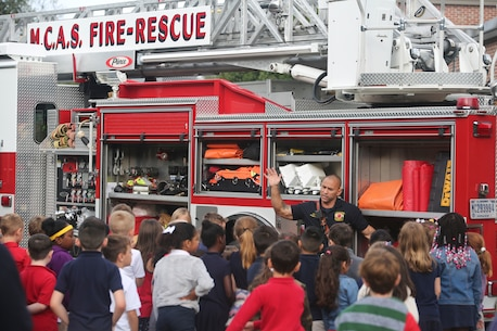 Capt. Bobby Clark gives a demonstration of tools and equipment to students at Elliott Elementary on Laurel Bay Oct. 9. The demonstration was held to educate the students about fire safety as well as fire prevention techniques in recognition of National Fire Prevention Week. Clark is a firefighter with MCAS Beaufort Fire.