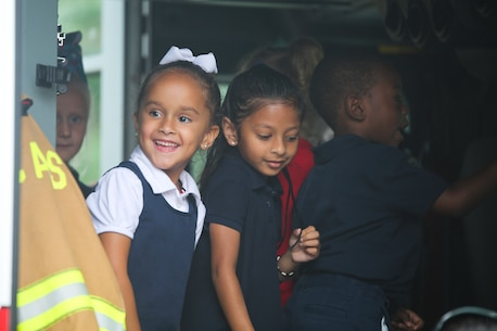 """Children at Elliott Elementary School get a tour of a fire truck on Laurel Bay, Oct. 9. The tour was held to educate the students about fire safety as well as fire prevention techniques in recognition of """"National Fire Prevention Week""""."""