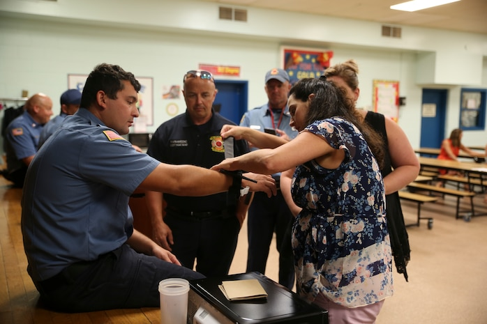 Robert Kometshcer instructs a teacher as she practices using a tourniquet on a paramedic at Bolden Elementary