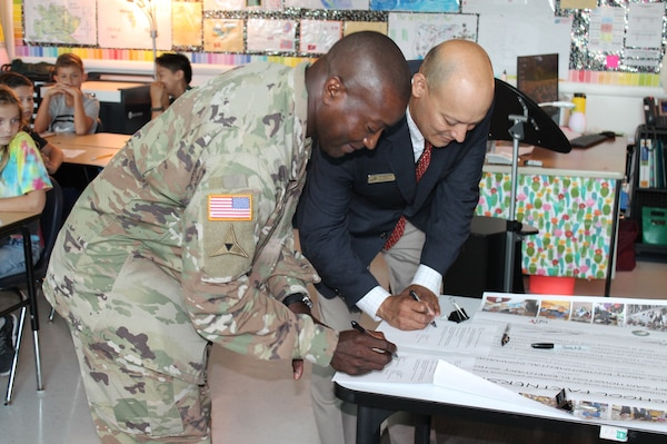 Col. Isaac Manigault (left), commander of the U.S. Army Environmental Command, and Dr. Joseph Cerna, Fort Sam Houston Elementary School principal, sign a renewal of the official charter for the Joint Base San Antonio-Fort Sam Houston Adopt-A-School Program partnership Oct. 3.