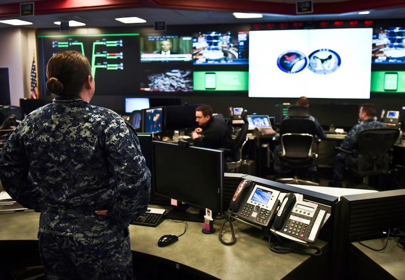 A sailor stands in an operations center-type room with a wall of screens and sailors seated at banks of computers.