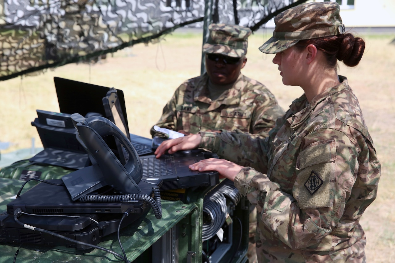 Two soldiers work on computers on a table outside in desert-type terrain.