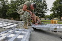 Army Sgt. 1st Class Brian Pitchford (left) and Chief Petty Officer Benjamin Allen (right) assemble ramps during an air load test Oct. 9, 2018 at the C-17 Training Area at Fort Eustis, Va. This test was part of an air load plan reconfiguration and verified that two box trucks can fit side-by-side on a Boeing C-17 Globemaster III. When directed, JTF-CS is ready to respond in 24 hours to provide command and control of 5,200 federal military forces located at more than 36 locations throughout the nation in support of civil authority response operations to save lives, prevent further injury and provide critical support to enable community recovery. (Official DoD photo by Mass Communication Specialist 3rd Class Michael Redd/released)