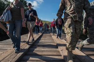 Members of the 97th Air Mobility Wing cross a bridge, during the Lake Altus-Lugert Dam tour, Oct. 5, 2018, in Lugert, Okla.