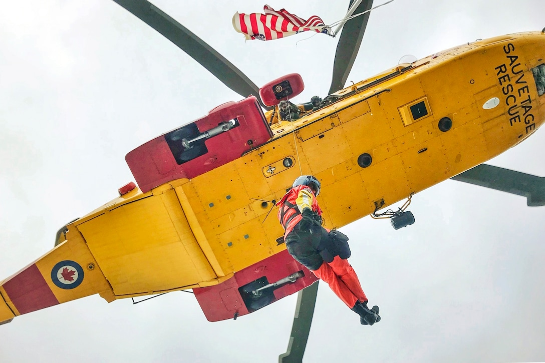 A Coast Guardsman, shown from below, hangs out of a yellow helicopter in flight.