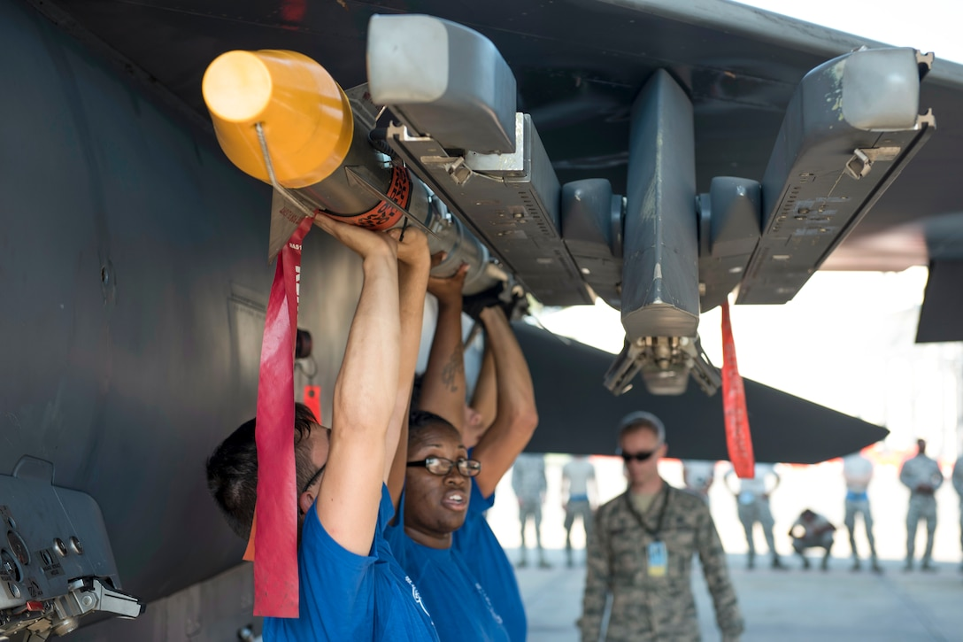 Airmen hoist a missile over their heads while attaching it to an aircraft wing.