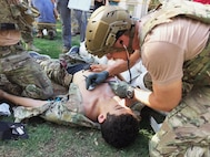 U.S. Air Force Pararescuemen, 304th Rescue Squadron Portland, Oregon, provide medical attention to Airman First Class James Pedrie, PJ Rodeo volunteer, for a simulated gunshot wound at the PJ Rodeo in San Antonio, Texas, Sept. 19, 2018. The PJ Rodeo provides comradery, networking opportunities, and serves as a source of additional training for competitors.