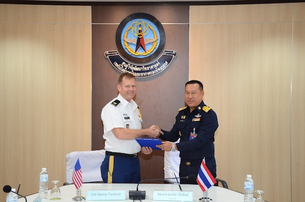 Royal Thailand Air Force Air Marshal Yuttachai Watcharasing (right) and U.S. Army Col. Wayne Turnbull, senior defense official and defense attaché to Thailand (left), celebrate the signing of an agreement for space situational awareness services and data, Oct. 1, 2018, in Thailand. Agreements like these bolster the United States and Thailand's awareness in the space domain. (Courtesy Photo)