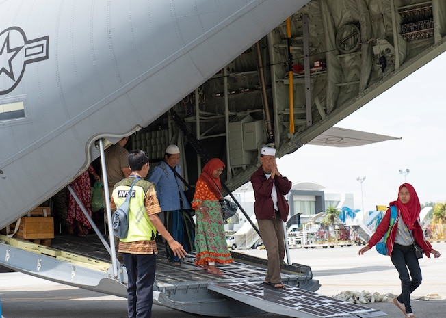 An Indonesian man raises his hands as a sign of thank you after landing at the airport in Balikpapan, Indonesia Oct. 9, 2018.