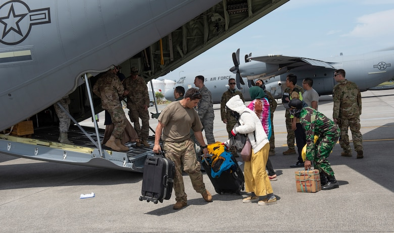 U.S. Air Force Staff Sgt. Roni Choueiry, 36th Contingency Response Group NCO in charge standards and evaluation, at Andersen Air Force Base, Guam helps an Indonesian woman with her luggage after a flight on a C-130 Hercules aircraft in Balikpapan, Indonesia Oct. 9, 2018.