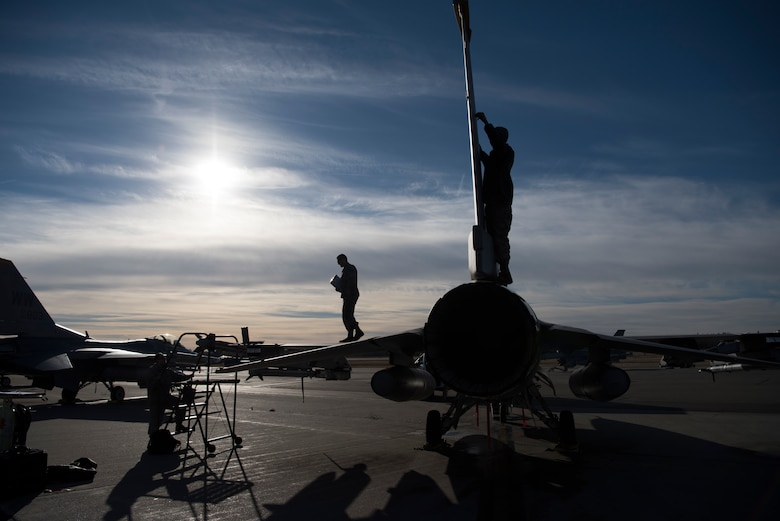 U.S. Air Force Tech. Sgt. Michael Zimmermann, a 13th Aircraft Maintenance Unit expeditor, left, walks across an F-16 Fighting Falcon wing, while Senior Airman Cody Fugate, center, a 13th Aircraft Maintenance Unit crew chief, makes a repair to the aircraft's panel during Exercise Red Flag-Alaska 19-1, at Eielson Air Force Base, Alaska, Oct. 9, 2018. Fugate is responsible for launching and recovering jets while performing routine maintenance such as tire inspections, damaged parts repair and administering hydro oil to the jet. (U.S. Air Force photo by Airman 1st Class Collette Brooks)