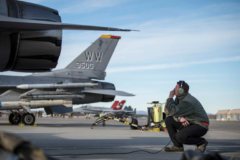 U.S. Air Force Airman 1st Class Kelsie Walls, a 13th Aircraft Maintenance Unit crew chief, communicates over a headset with a pilot prior to take-off during exercise Red Flag-Alaska 19-1, at Eielson Air Force Base, Alaska, Oct. 9, 2018. Maintainers repair jets alongside joint and multilateral partners from around the world affording them opportunities to exchange tactics, operations techniques and procedures which improves international interoperability. (U.S. Air Force photo by Airman 1st Class Collette Brooks)