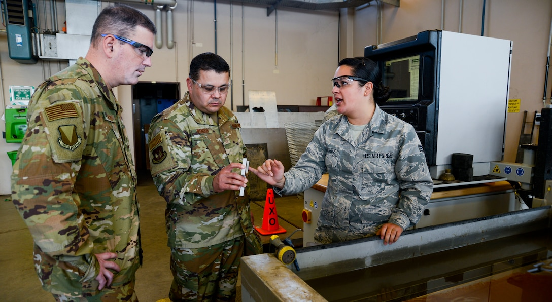 U.S. Air Force Brig. Gen. Mark R. August, 86th Airlift Wing commander, and Chief Master Sgt. Ernesto J. Rendon Jr., 86th AW command chief, view an item the 86th Maintenance Squadron Metals Technology Flight created using a water jet cutting machine during an immersion tour of the 86th Maintenance Group on Ramstein Air Base, Germany, Oct. 9, 2018. The command team used the immersion as a way to get a better understanding of the 86th MXG's capabilities as well as a way for Airmen to ask questions directly to the wing leaders. (U.S. Air Force photo by Staff Sgt. Timothy Moore)