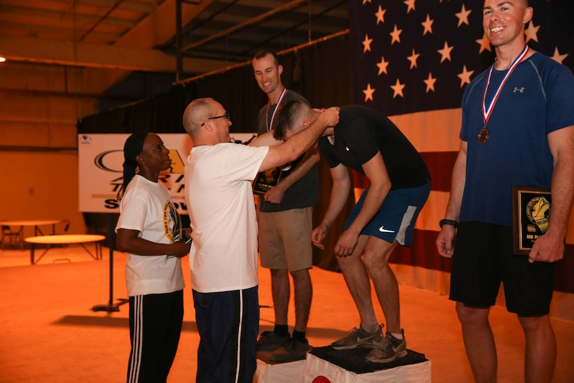 U.S. Army Soldiers receive medals and plaques for finishing in the top three for the men's category during the Army Ten-Miler at Camp As-Sayliyah, Qatar, October 7, 2018.  The awards ceremony recognized these individuals for their impressive athleticism.