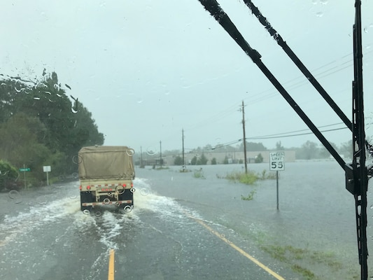 Virginia National Guard Soldiers assigned to the Virginia Beach-based 1173rd Transportation Company drive through high water to deliver supplies to shelters Sept. 17, 2018, in North Carolina.