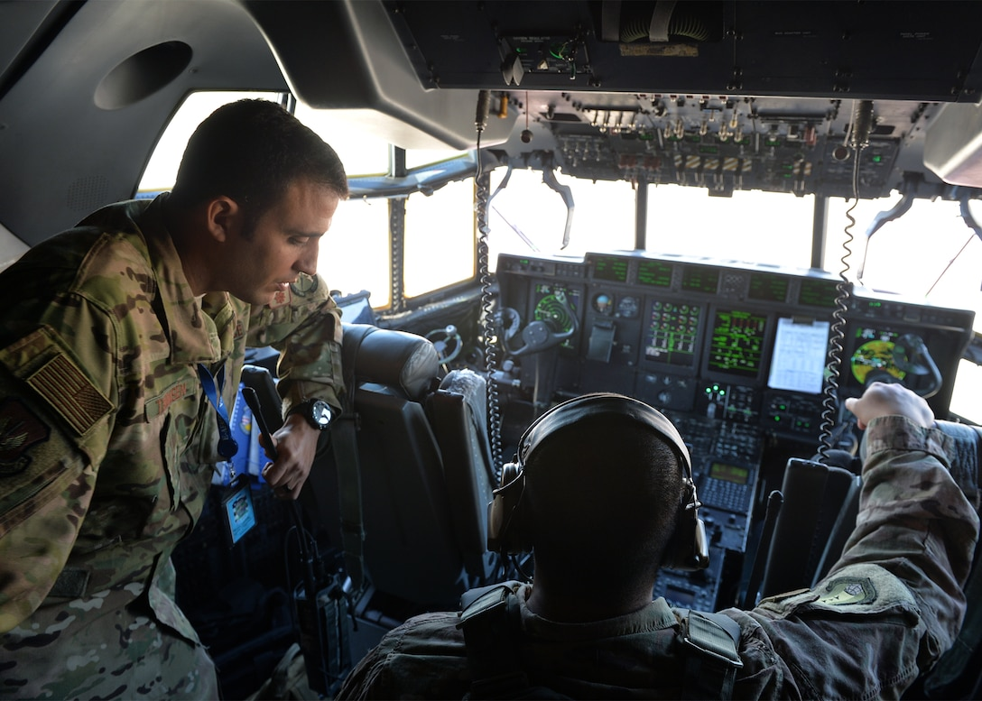 "U.S. Air Force Maj. Christopher Thomsen, 435th Contingency Response Squadron director of operations, and Senior Airman Andrew Domingo, 435th CRS C-130J Super Hercules crew chief, monitor gauges as a C-130J is de-fueled on Ramstein Air Base, Germany. As part of an exercise, members of the 435th Contingency Response Group defueled a C-130J and performed a ""hot refuel"" on two F-16 Fighting Falcon aircraft. (U.S. Air Force photo by Staff Sgt. Jimmie D. Pike)"