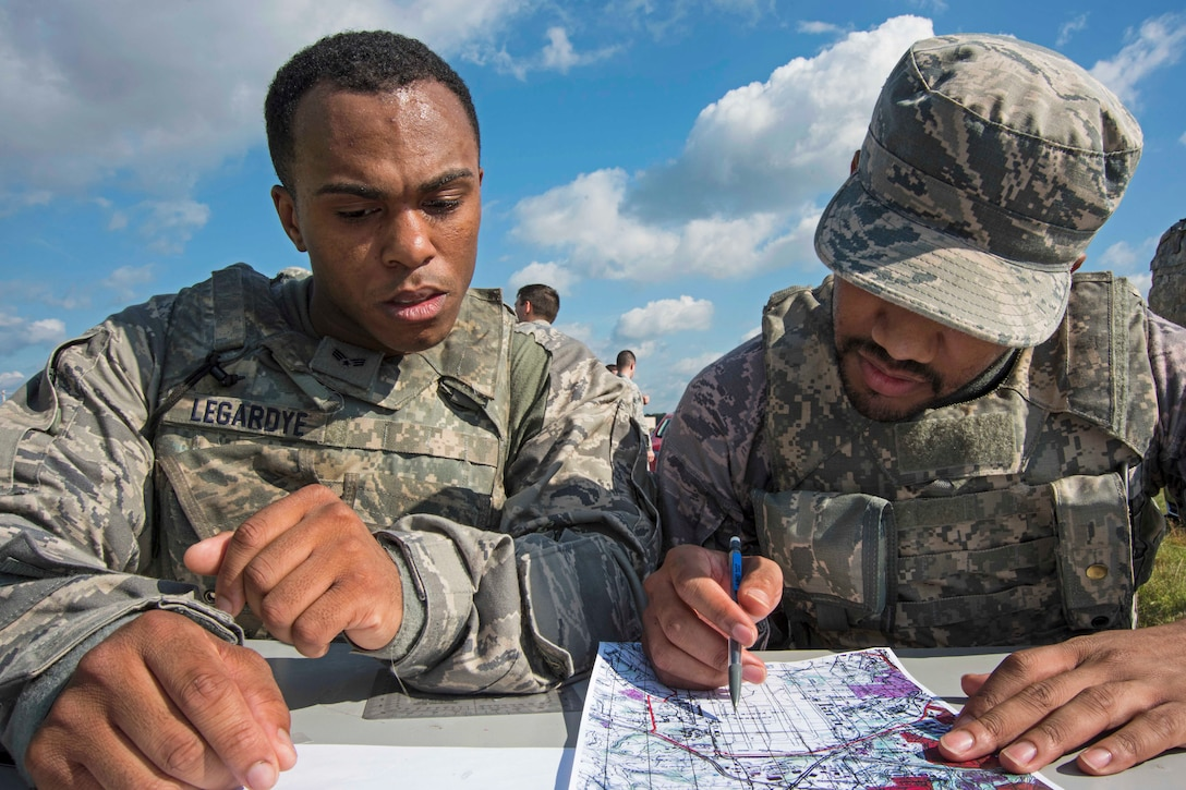 Senior Airmen Aaron Legardye, left, and Anthony Poindexter, 11th Security Forces Squadron response force members, participate in a land navigation exercise during the 11th SFS Defender's Challenge on Joint Base Andrews, Md., Oct. 3, 2018. The challenge tested the defenders' physically, as well as, mentally, in weapons knowledge, urban tactics, land navigation, self-aid buddy care and response to attacks. (U.S. Air Force photo by Airman 1st Class Michael S. Murphy)