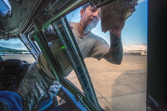 Staff Sgt. John P. Casey, 514th Aircraft Maintenance Squadron flying crew chief, cleans the cockpit windows of a C-17 Globemaster III at Barbers Point, Hawaii, prior to the return trip to Joint Base McGuire-Dix-Lakehurst, N.J., Oct. 7, 2018, after a joint training mission with the 514th Aeromedical Evacuation Squadron, 45th AES and the 439th AES at Barbers Point. (U.S. Air Force photo by Master Sgt. Mark C. Olsen)
