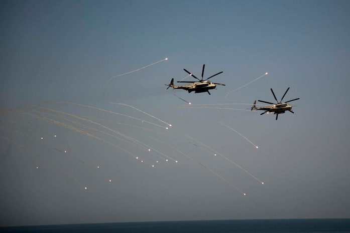 ARABIAN SEA-Two CH-53E Super Stallion Helicopters with Marine Medium Tiltrotor Squadron 166 Reinforced, 13th Marine Expeditionary Unit, launch flares during a training exercise, Oct. 7, 2018. The Essex is the flagship for the Essex Amphibious Ready Group and, with the embarked 13th MEU, is deployed to the U.S. Fifth Fleet area of operations in support of naval operations to ensure maritime stability and security in the Central Region, connecting the Mediterranean and the Pacific through the western Indian Ocean and three strategic choke points.