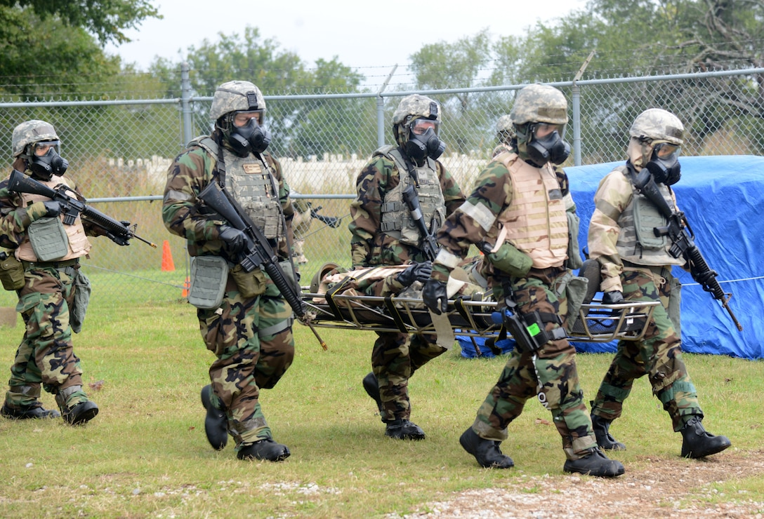 A team participating in the CBRNE exercise carry an injured dummy on a litter to a checkpoint after administering self-aid buddy care. Knowing how to correctly assess injuries, whether critical or fatal, and then help the wounded victim without creating more harm, is an important component during these kinds of exercises.