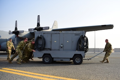 Maintainers from the 386th Expeditionary Aircraft Maintenance Squadron drag a ground power unit away from a 43rd Expeditionary Electronic Combat Squadron EC-130 aircraft Sept. 21, 2018, at an undisclosed location in Southwest Asia. The EC-130 aircraft serves as a tactical weapon system since 1981 and has been modified through the years. Each update has provided the platform stronger avionics systems, radars and more powerful digital signal analysis computers and subsystems. (U.S. Air Force photo by Staff Sgt. Christopher Stoltz)