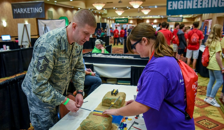 Senior Master Sgt. Thomas Ryan, 14th Civil Engineer Squadron superintendent, works on building a bridge with a student Oct. 2, 2018, during the Imagine the Possibilities Career Expo at the BancorpSouth Arena in Tupelo, Mississippi. More than 120 Airmen from Columbus AFB, Mississippi, spent several days showing more than 7,000 eighth-grade students, from northeast Mississippi counties, some of the vast career opportunities the Air Force offers. (U.S. Air Force photo by Tech. Sgt. Christopher Gross)
