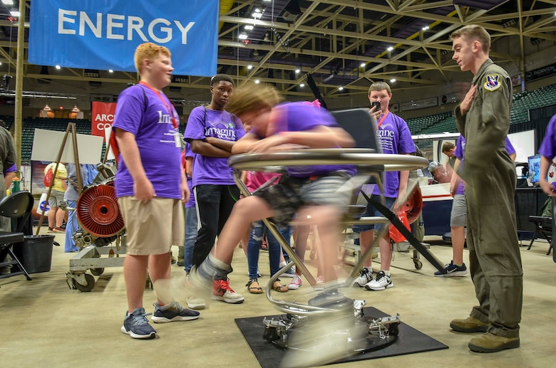Airman 1st Class Anthony Halas, 14th Medical Operations Squadron, spins a student in a Barany Chair Oct. 2, 2018, during the Imagine the Possibilities Career Expo at the BancorpSouth Arena in Tupelo, Mississippi. More than 120 Airmen from Columbus AFB, Mississippi, spent several days showing more than 7,000 eighth-grade students, from northeast Mississippi counties, some of the vast career opportunities the Air Force offers. (U.S. Air Force photo by Tech. Sgt. Christopher Gross)