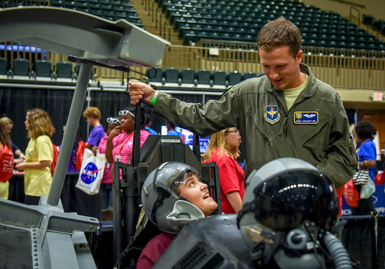 Capt. Mike Crampton, 37th Flying Training Squadron instructor pilot, sits by a student in a model T-6 Texan II cockpit Oct. 2, 2018, during the Imagine the Possibilities Career Expo at the BancorpSouth Arena in Tupelo, Mississippi. More than 120 Airmen from Columbus AFB, Mississippi, spent several days showing more than 7,000 eighth-grade students, from northeast Mississippi counties, some of the vast career opportunities the Air Force offers. (U.S. Air Force photo by Tech. Sgt. Christopher Gross)
