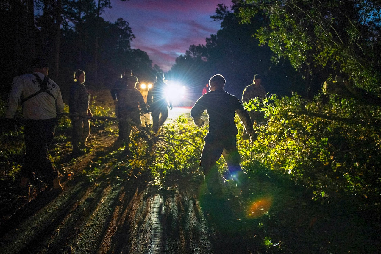 Several guardsmen clear brush and downed trees from a road at night.
