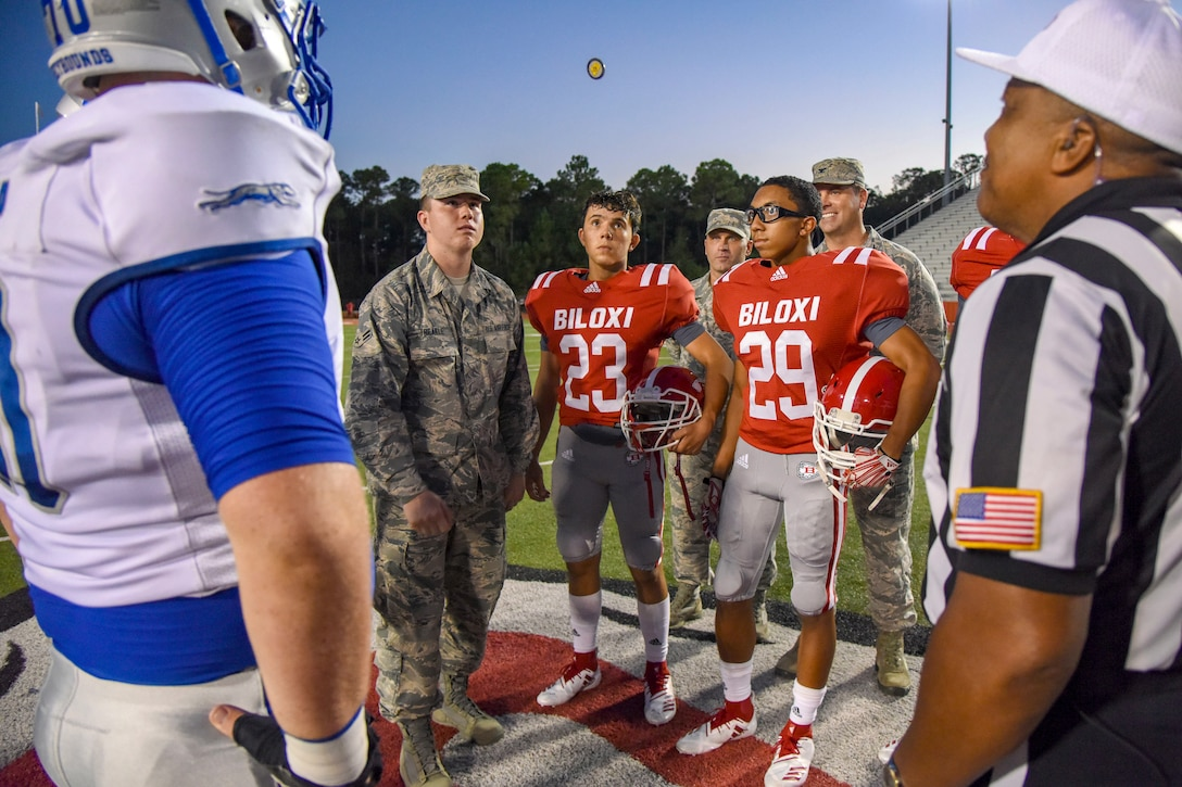High school football players, a referee, and an airmen watch a coin flip through the air before a football game.