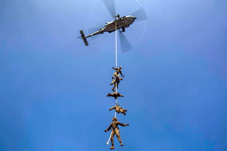Five Marines, bound to a rope, hang midair, carried by a helicopter.