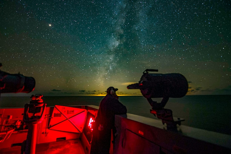 A sailor peers out over the open sea at night.