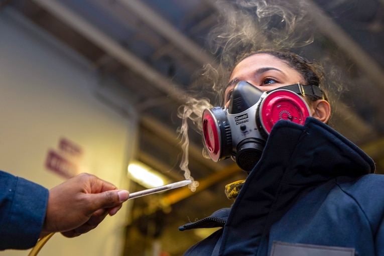 A sailor wears a breathing mask while another sailor waves a burning stick near the mask.