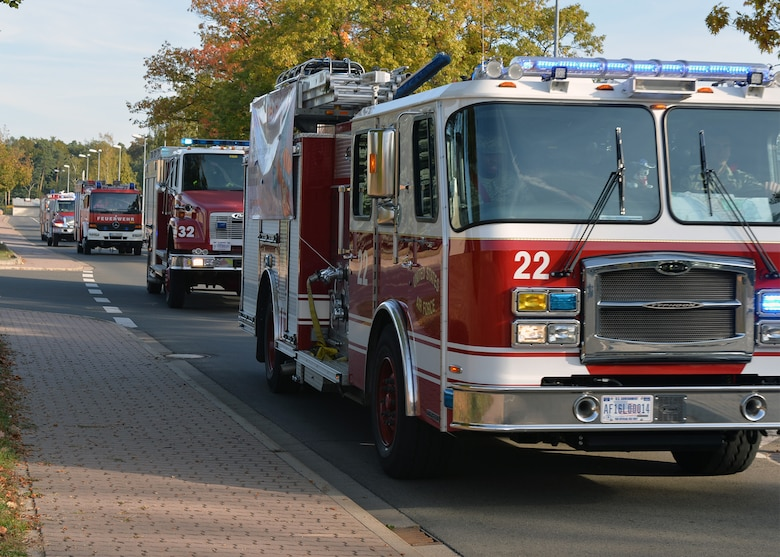 Firefighters from the Kaiserslautern Military Community Fire and Emergency Services drive fire trucks by base housing on Ramstein Air Base, Germany, Oct. 6, 2018. Fire trucks were part of a parade to kick off Fire Prevention Week on Ramstein, observed from Oct. 7 - 13. (U.S. Air Force photo by Staff Sgt. Jimmie D. Pike)
