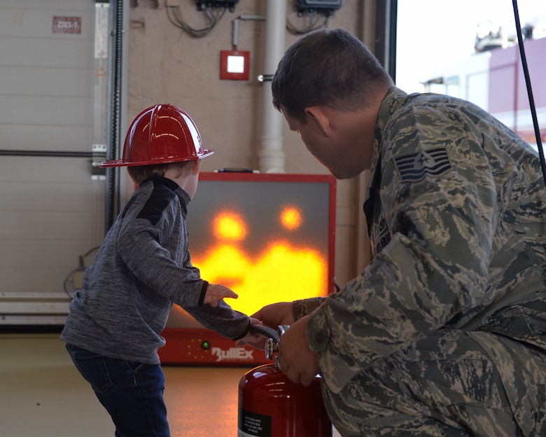 U.S. Air Force Tech. Sgt. James Fligor, 86th Civil Engineer Squadron Station 3 station chief, helps a child put out a simulated fire on a fire extinguisher trainer on Ramstein Air Base, Germany, Oct. 6, 2018. Members of the Kaiserslautern Military Community Fire and Emergency Services came together during Fire Prevention Week to help raise awareness of the importance of fire safety. (U.S. Air Force photo by Staff Sgt. Jimmie D. Pike)