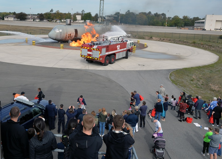 Attendees watch as firefighters assigned to the 86th Civil Engineer Squadron fight a simulated aircraft fire on Ramstein Air Base, Germany, Oct. 6, 2018. Firefighters demonstrated their capabilities for members of the Kaiserslautern Military Community as part of the fire department's open house to kick off Fire Prevention Week. (U.S. Air Force photo by Staff Sgt. Jimmie D. Pike)