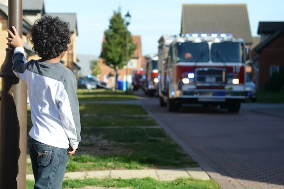 A child observes a fire truck parade at Royal Air Force Lakenheath, England, Oct.12, 2018. The 48th Civil Engineer Squadron hosted several events throughout the week in recognition of Fire Prevention Week. (U.S.Air Force photo/Airman 1st Class Shanice Williams-Jones)