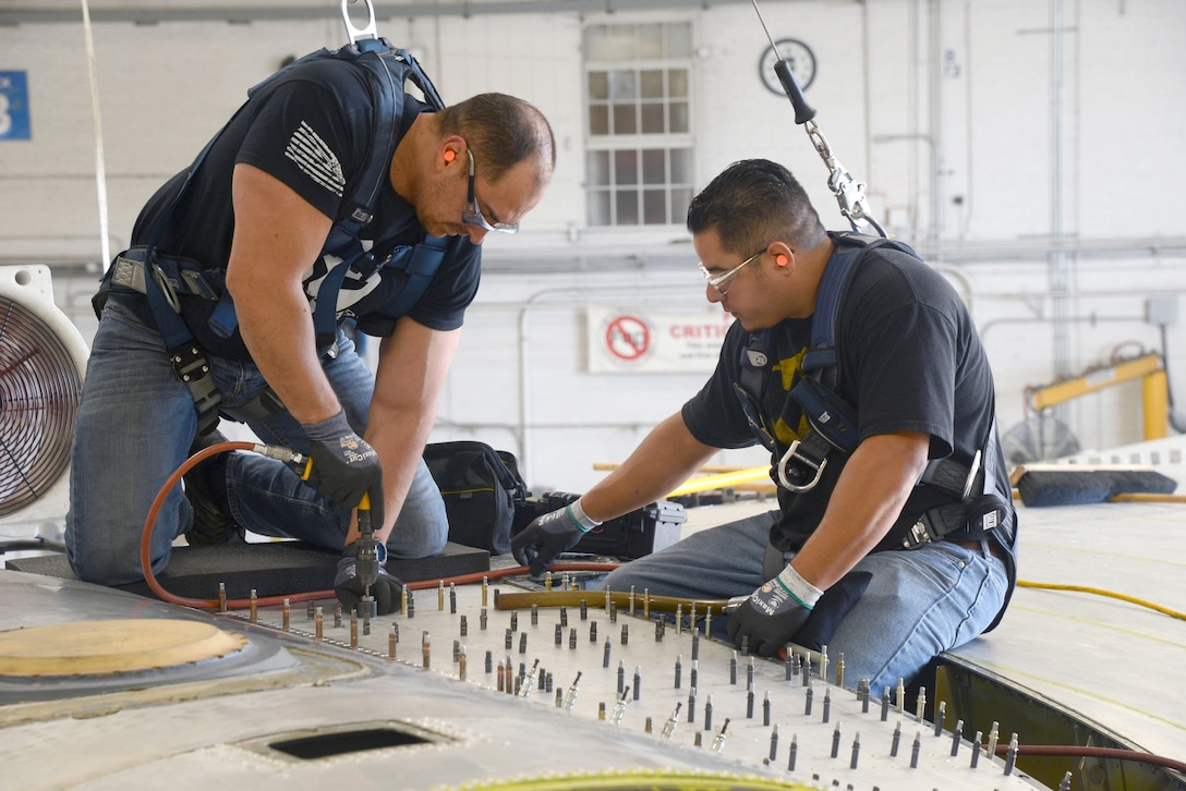 David Leon and Adrian Martinez, sheetmetal mechanics with the 565th Aircraft Maintenance Squadron, work on the stub longeron of the B-52.