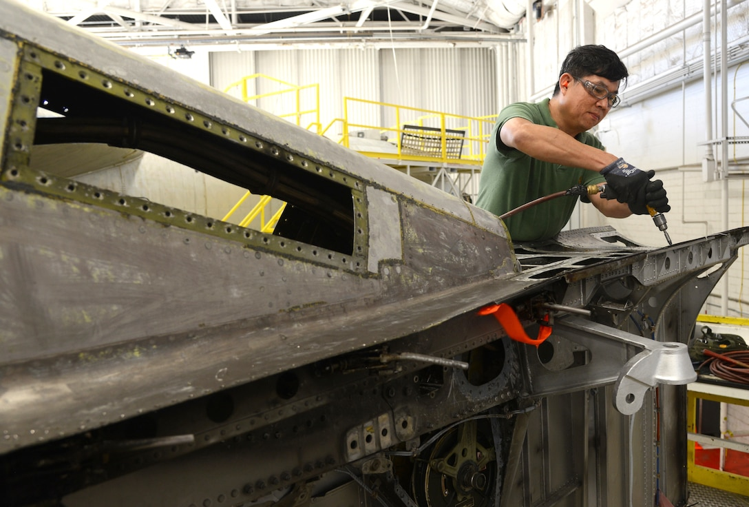 Khoi Le, a sheetmetal mechanic with the 565th Aircraft Maintenance Squadron, drills rivets into an engine strut of a B-52 Stratofortress as part of programmed depot maintenance.