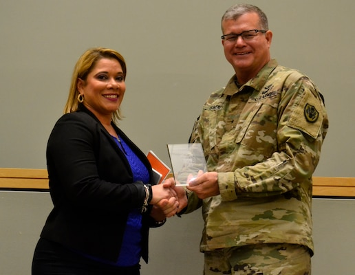 Joanna Otero-Cruz receives an award from Army Brig. Gen. Mark Simerly, DLA Troop commander, during this year's Hispanic Heritage Month program in Philadelphia October 11, 2018.