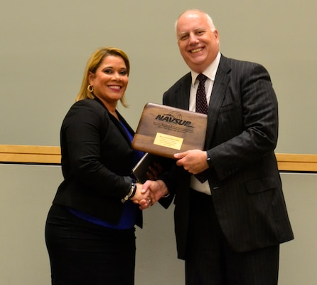 Joanna Otero-Cruz receives an award from Kurt Wendelken, NAVSUP-WSS acting vice-commander, during this year's Hispanic Heritage Month program in Philadelphia October 11, 2018.