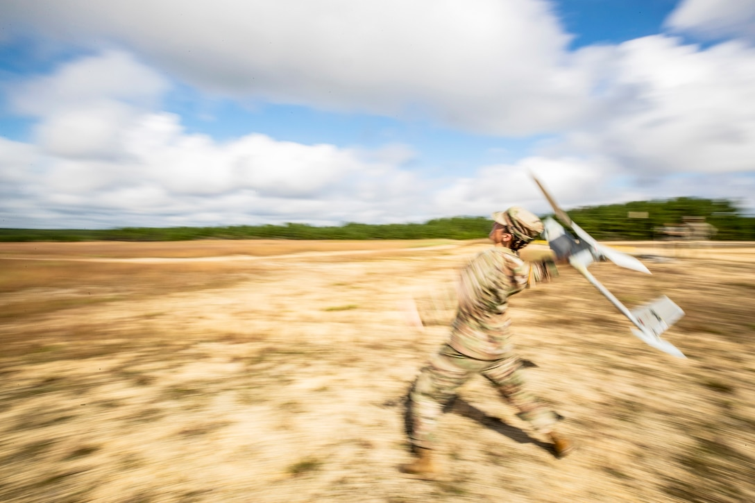 A soldier prepares to throw a drone aircraft in a field.