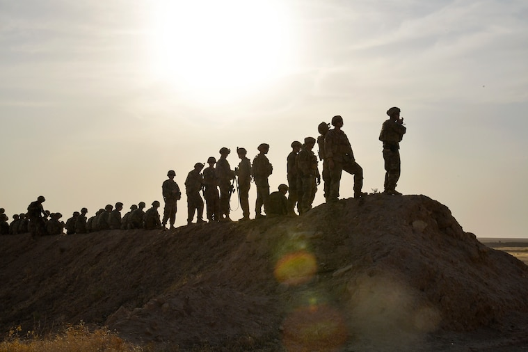 More than a dozen soldiers, shown in silhouette, stand and look out on a hill.