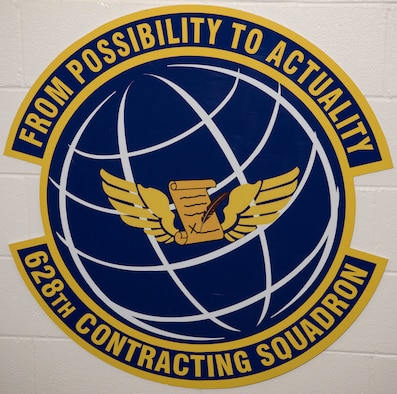 The 628th Contracting Squadron emblem is posted on the wall in the squadron.