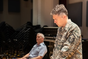 Staff Arranger Master Sgt. John Bliss overlooks a score to one of his arrangements during a rehearsal for the Fall 2019 tour